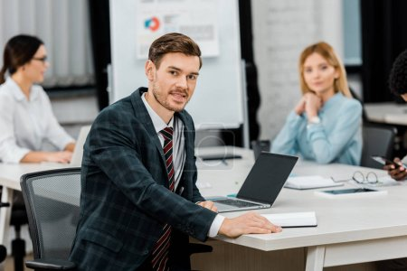 selective focus of young businessman in suit and multiracial colleagues in office