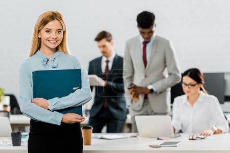 Photo pour Mise au point sélective de femme d'affaires avec dossier et multiethniques collègues de bureau - image libre de droit
