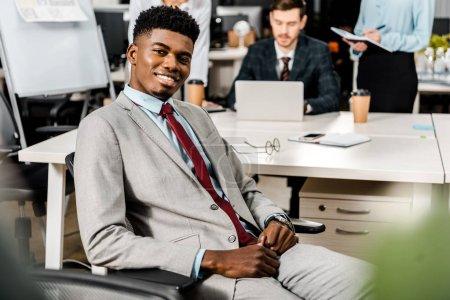Photo pour Mise au point sélective du sourire, homme d'affaires américain africain et ses collègues derrière au lieu de travail au bureau - image libre de droit