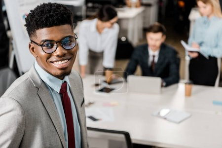 selective focus of smiling african american businessman and colleagues behind at workplace in office