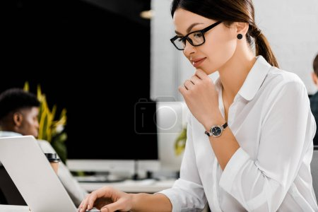 young businesswoman in eyeglasses working on laptop at workplace in office