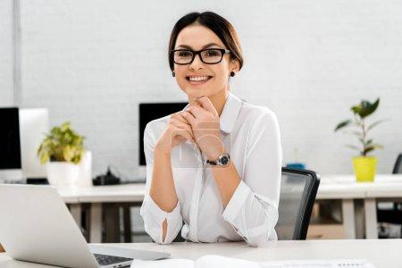 retrato de mujer de negocios sonriente en gafas en el lugar de trabajo con computadora portátil en la oficina