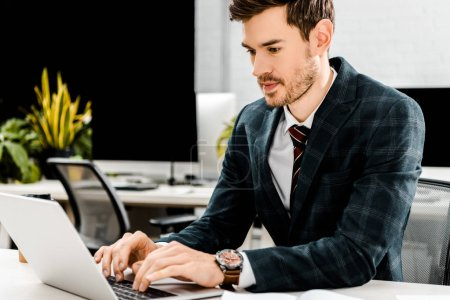 Photo for Young businessman in suit working on laptop at workplace in office - Royalty Free Image