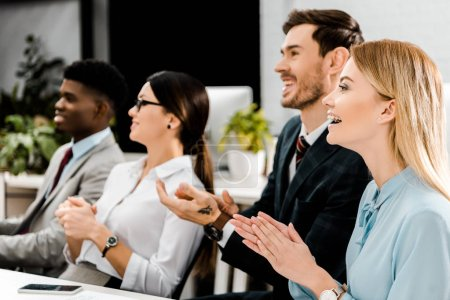 Photo for Smiling multiracial businesspeople applauding to speaker in office - Royalty Free Image
