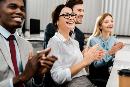 smiling multiracial businesspeople applauding to speaker in office