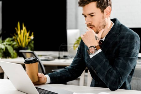 Photo for Pensive businessman with coffee to go looking at laptop at workplace in offce - Royalty Free Image