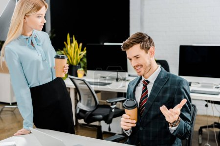 young business colleagues with coffee to go having conversation in office