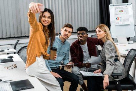 Foto de Sonrientes multiculturales empresarios tomar selfie en smartphone durante el trabajo en la oficina - Imagen libre de derechos