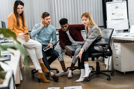 Photo for Multicultural young businesspeople discussing new business idea in office - Royalty Free Image