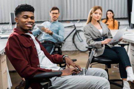 Photo pour Multiculturels jeunes entrepreneurs avec les papiers et les dispositifs numériques dans office - image libre de droit