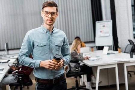 Foto de Enfoque selectivo del joven empresario con café para ir en la oficina con compañeros multirraciales detrás - Imagen libre de derechos