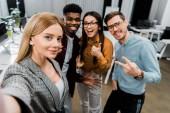 """Постер, картина, фотообои """"точки зрения камеры улыбаясь многокультурном коллеги принимая selfie вместе в офисе"""""""