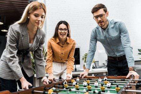 Photo pour Collègues de travail joyeux jouant au football de table ensemble au bureau - image libre de droit