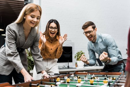 Photo for Cheerful business colleagues playing table football together in office - Royalty Free Image