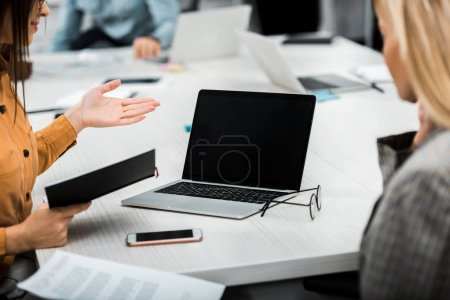 Photo for Partial view of businesswomen working on project together at workplace with laptop in office - Royalty Free Image