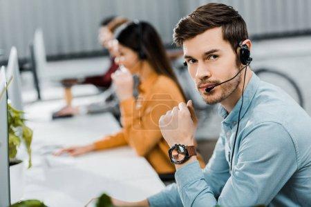 Photo pour Foyer sélectif de l'opérateur de centre d'appel dans le casque dans le bureau - image libre de droit