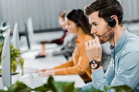 Photo pour Mise au point sélective d'opérateur de centre d'appel dans l'oreillette au bureau - image libre de droit