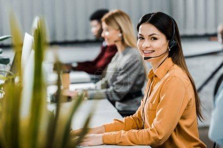 Photo pour Opérateurs de centres d'appel multiculturelle avec casques d'écoute à workpalce au bureau - image libre de droit