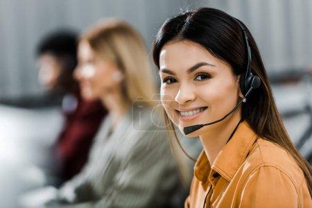 Foto de Enfoque selectivo de sonriente operador femenina llamada en el microcasco en la oficina - Imagen libre de derechos