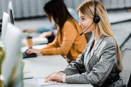 Photo pour Foyer sélectif de sourire opérateur de centre d'appels travaillant dans le bureau - image libre de droit