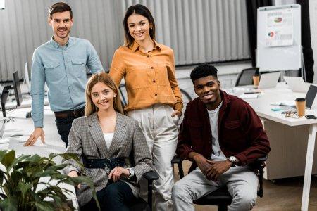 Photo pour Jeunes souriants multiraciaux collègues d'affaires regardant la caméra dans le bureau - image libre de droit
