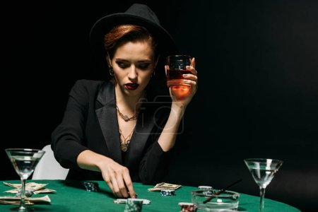 beautiful girl in jacket and hat holding glass of whiskey and playing poker in casino
