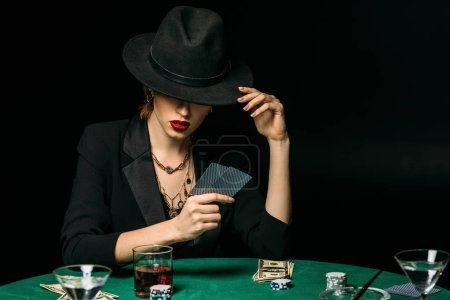 attractive girl in jacket and hat playing poker in casino