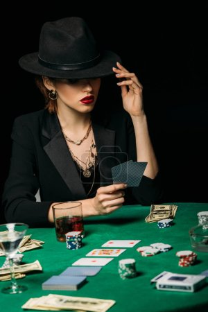 attractive girl in jacket and hat playing poker and holding cards in casino