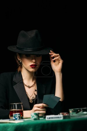 Photo for Surface level of attractive girl in jacket touching hat playing poker in casino - Royalty Free Image