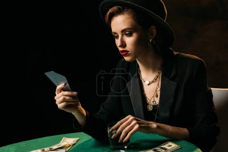 attractive girl in jacket and hat looking at poker cards and holding glass of whiskey in casino