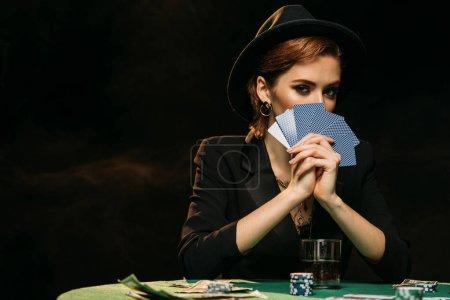 Foto de Chica atractiva en la chaqueta y sombrero que cubre la cara con cartas de poker y mirando a cámara en casino - Imagen libre de derechos