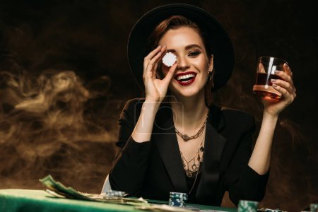 happy attractive girl in jacket and hat holding glass of whiskey at poker table and covering eye with casino chip
