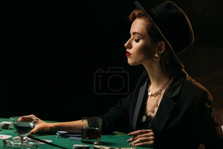 side view of attractive girl in jacket and hat sitting at poker table in casino