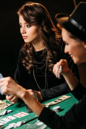 beautiful women playing poker with cards and chips at table in casino