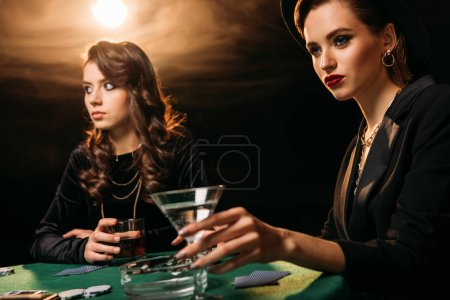 attractive girls playing poker at table in casino, woman holding glass of cocktail