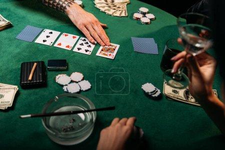 Foto de Imagen recortada de mujer y hombre tatuado jugar mesa de poker en el casino, chica sosteniendo la Copa de Cóctel - Imagen libre de derechos