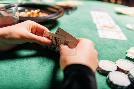 cropped image of girl holding poker cards at table in casino