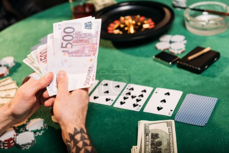 cropped image of tattooed man holding cash at poker table in casino