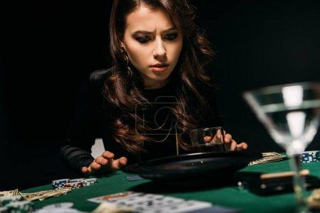 Foto de Chica atractiva concentrada mirando a la ruleta en la mesa en el casino - Imagen libre de derechos