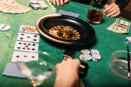 cropped image of girls playing roulette at poker table in casino