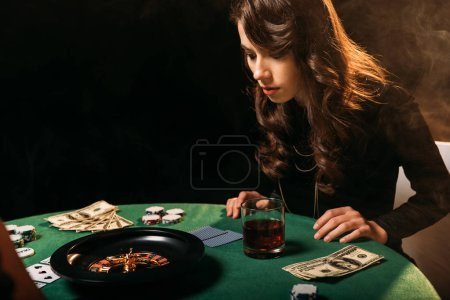 focused attractive girl looking at roulette at table in casino