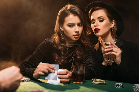 serious attractive girls playing poker at table in casino