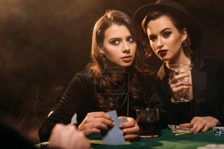 Foto de Mujeres hermosas jugando al póker en la mesa de casino y mirando lejos - Imagen libre de derechos