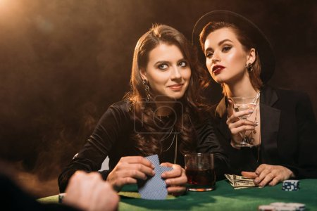 Photo for Cheerful attractive girls playing poker at table in casino - Royalty Free Image