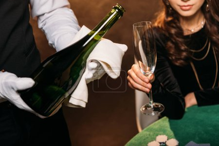 Photo for Cropped image of waiter pouring champagne in glass for girl at poker table in casino - Royalty Free Image