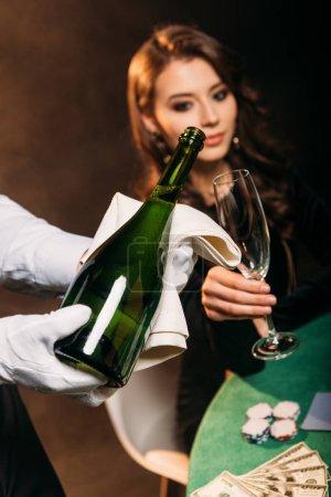 Photo pour Mise au point sélective de garçon coulée de champagne en verre pour jolie jeune fille à la table de poker au casino - image libre de droit