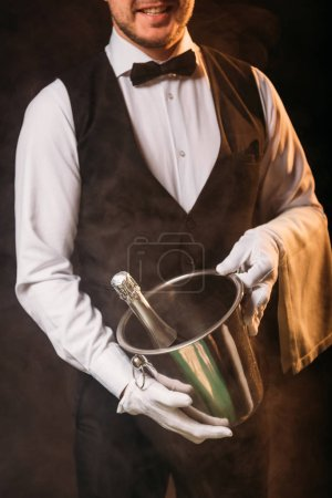 cropped image of smiling waiter holding bottle of champagne in bucket on black