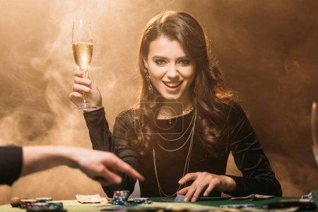 Foto de Atractiva chica feliz con Copa de champán en la mesa de póker en casino y mirando a cámara - Imagen libre de derechos