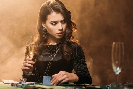 Foto de Chica atractiva irritada con Copa de champán en la mesa de póker en casino y mirando lejos - Imagen libre de derechos