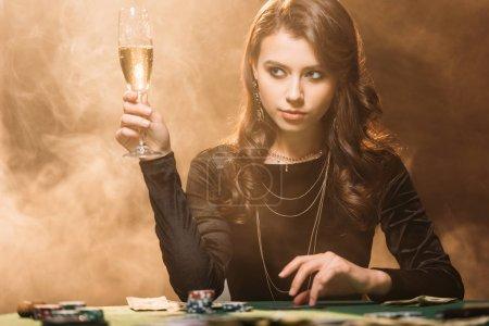 Foto de Hermosa mujer con Copa de champán en la mesa de póker en casino y mirando lejos - Imagen libre de derechos